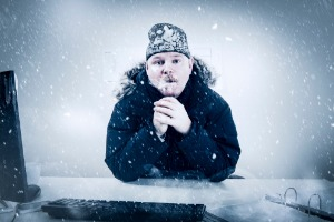 Man shivering at his desk in his freezing office because he needs furnace repair from STAATS Service Today in Creve Coeur, IL