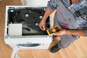 Appliance repair technician from STAATS Service Today fixing a washing machine in Creve Coeur, IL