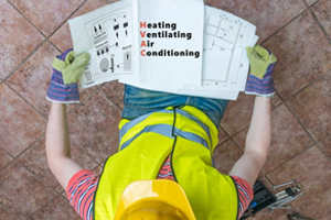 Worker of STAATS Service Today reading a manual about HVAC installation in Creve Coeur, IL